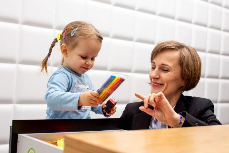 dziecko trzymające flamastry z uśmiechniętą kobietą