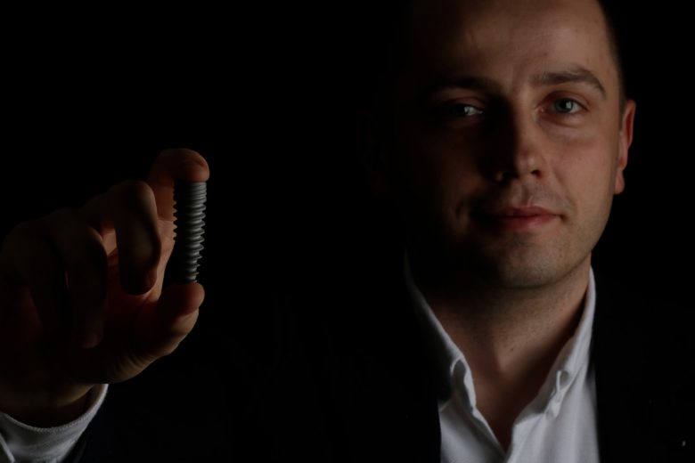 facet w czerni trzyma w ręce implant