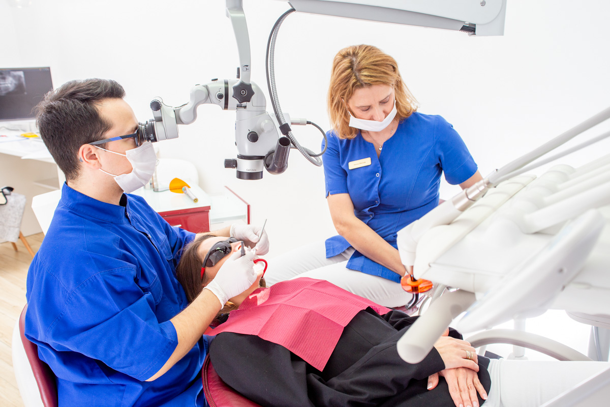 stomatolog wykonuje leczenie zachowawcze u pacjenta
