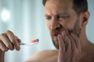mężczyzna z bólem zęba trzymający szczoteczke