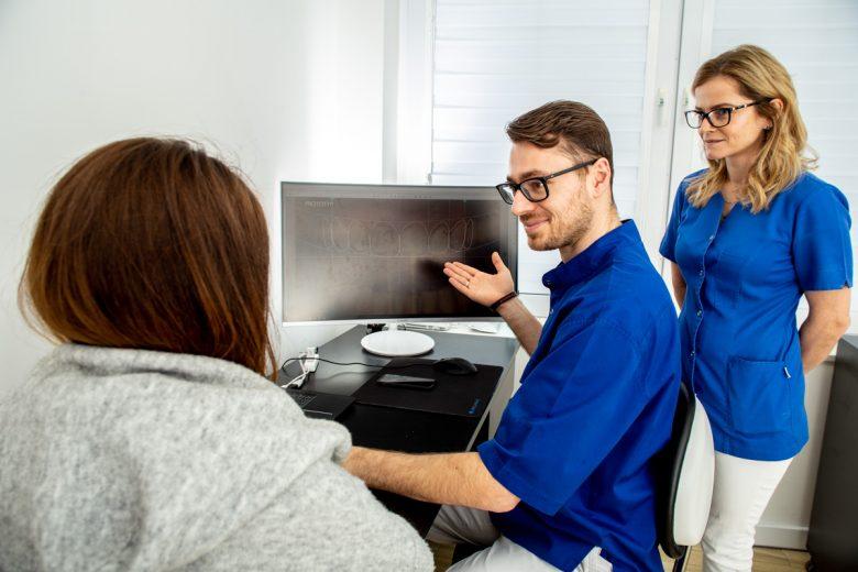 stomatolog pokazujący na ekranie zdjęcie zębów pacjenta