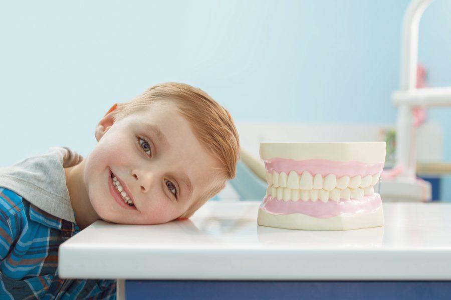 uśmiechnięte dziecko lęzące głowa na stole na którym jest sztuczna szczęka